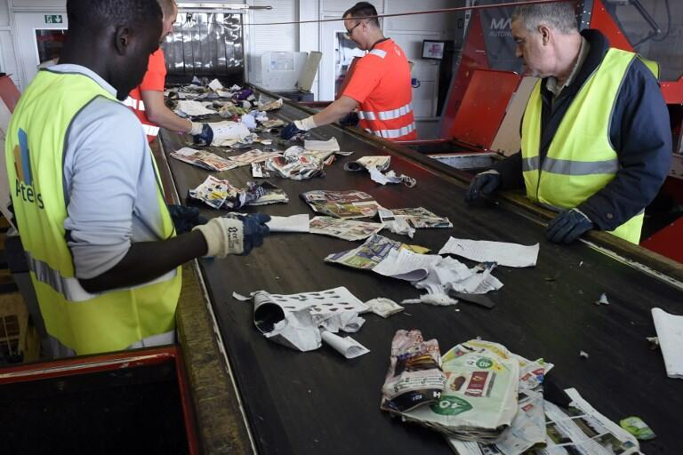 Veolia employees sort waste before being treated by a waste sorting robot on October 10, 2018 during a press visit held to present the new autonomous Max-AI sorting robot to be used at a factory of the French waste management company Veolia in Amiens.