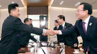 Les délégués de Corée du Nord (à gauche) et leurs homologues du Sud se serrent la main, lors d'une réunion à Panmunjom, le 17 janvier 2018.