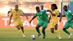 Le Sénégalais Keïta Baldé pris au marquage par deux Béninois.
