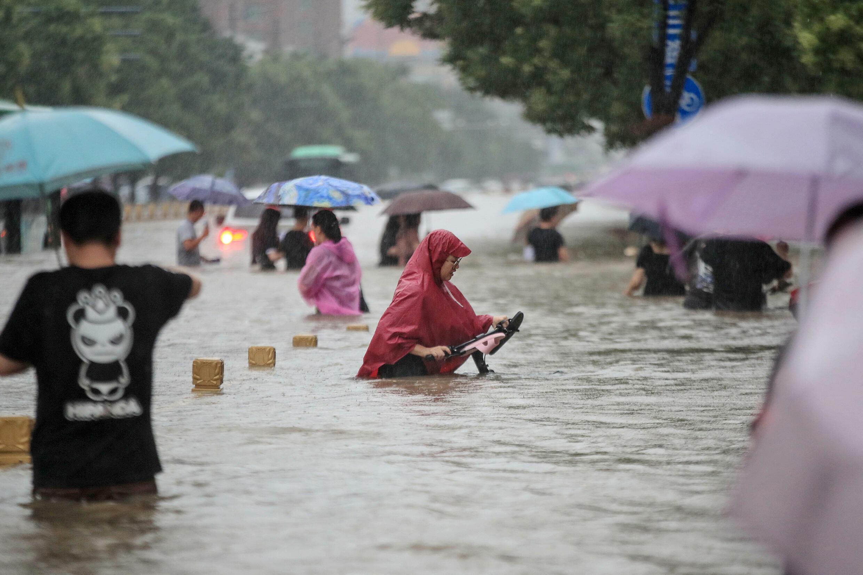 Gente atrapada por las aguas en una calle de Zhengzhou, centro de China, el 20 de julio de 2021