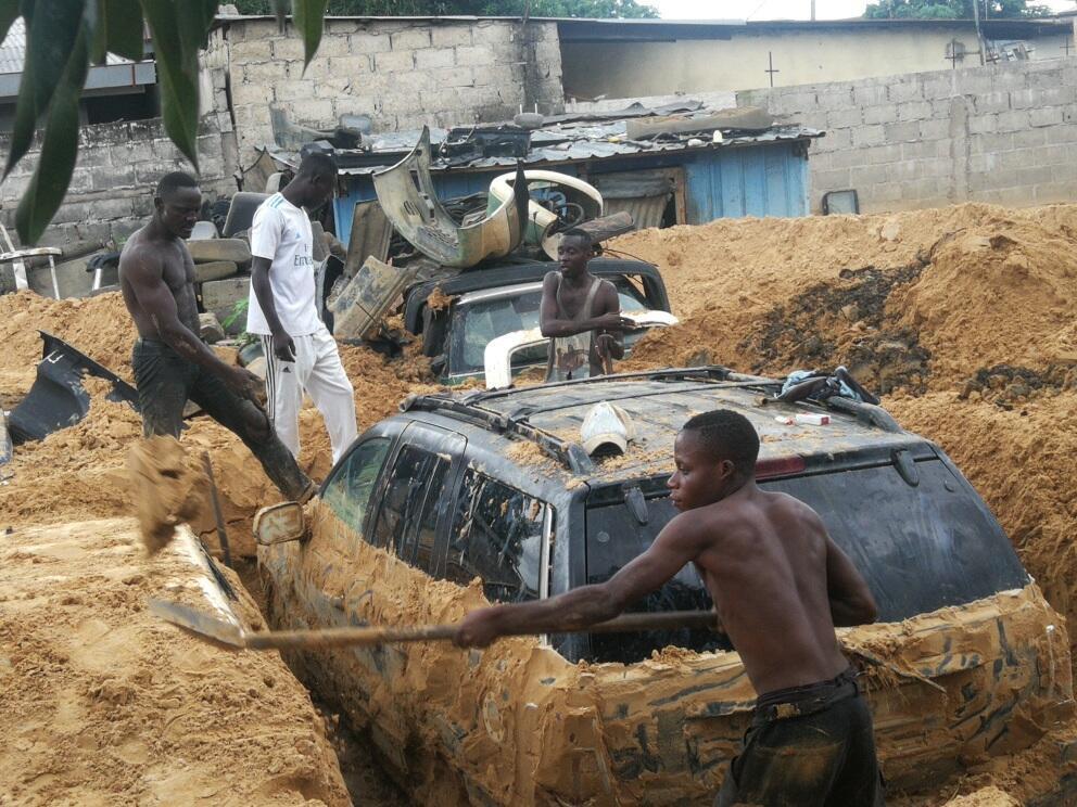 De jeunes Congolais dégagent une voiture engloutie après les précipitations à Brazzaville, le 9 décembre 2019.