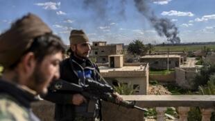 Des membres des Forces démocratiques syriennes (FDS) montent la garde sur le toit d'un bâtiment de la ville de Baghouz, le 3 mars 2019.