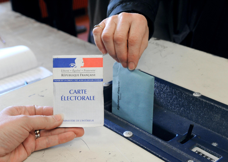 Un électeur dépose son bulletin dans l'urne dans un bureau de vote.
