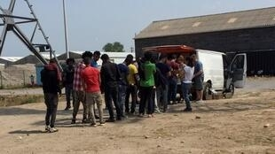 Des migrants font la queue pour la distribution de nourriture à Calais, le 21 juin 2017.