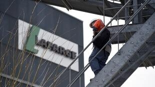 A worker walks down stairs outside a plant of French cement company Lafarge on April 7, 2014 in Paris.