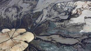 Le pétrole entre dans un bassin de résidus miniers aux exploitations de sables bitumineux de Suncor près de Fort McMurray, en Alberta au Canada (image d'illustration).
