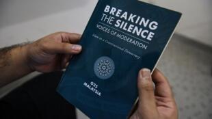 """នៅគូឡាឡាំពួរ បុរសម៉ាឡេស៊ីម្នាក់កាន់សៀវភៅ ឈ្មោះ """"Breaking The Silence: Voices Of Moderation - Islam In A Constitutional Democracy"""" ដែលនិយាយពីអ៊ីស្លាមមិនជ្រុលនិយម"""