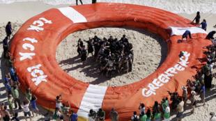 Militantes do Greenpeace fazem manifestação em praia de Cancún (México) durante conferência da ONU.