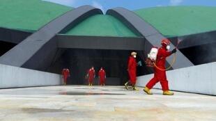 Des pompiers portant des combinaisons de protection pulvérisent du désinfectant au Parlement indonésien, à Jakarta, le 9 août 2020 (photo d'illustration).