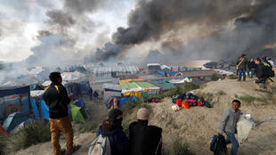 Smoke rises the sky as migrants and journalists look at burning makeshift shelters and tents in the 'Jungle' on the third day of their evacuation and transfer to reception centers in France last October.