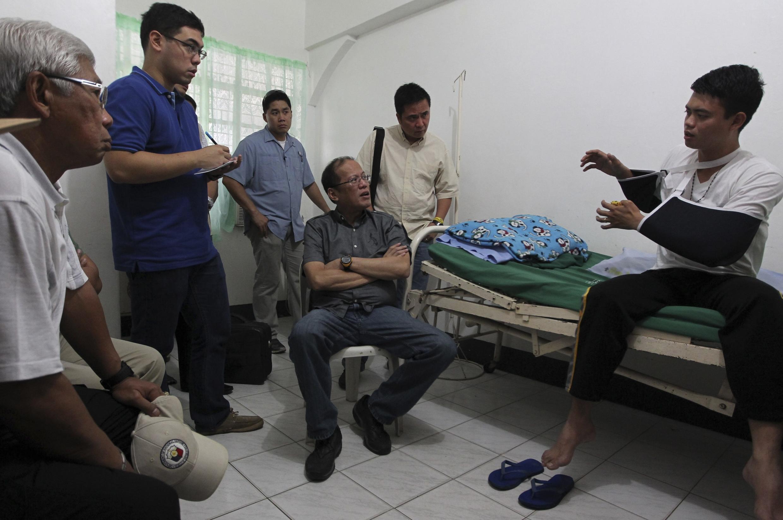 Tổng thốn Benigno Aquino (giữa) và các thành viên chính phủ khác, nghe ông Jun Abrasado, phụ tá bộ trưởng, người duy nhất sống sót, kể lại biến cố máy bay rơi, bệnh viện tỉnh Masbate, 19/08/2012.
