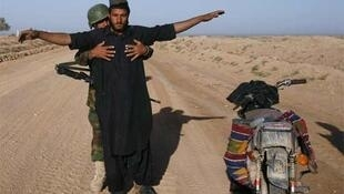 An Afghan national is searched by a member of the Afghan National Army in Marjah district