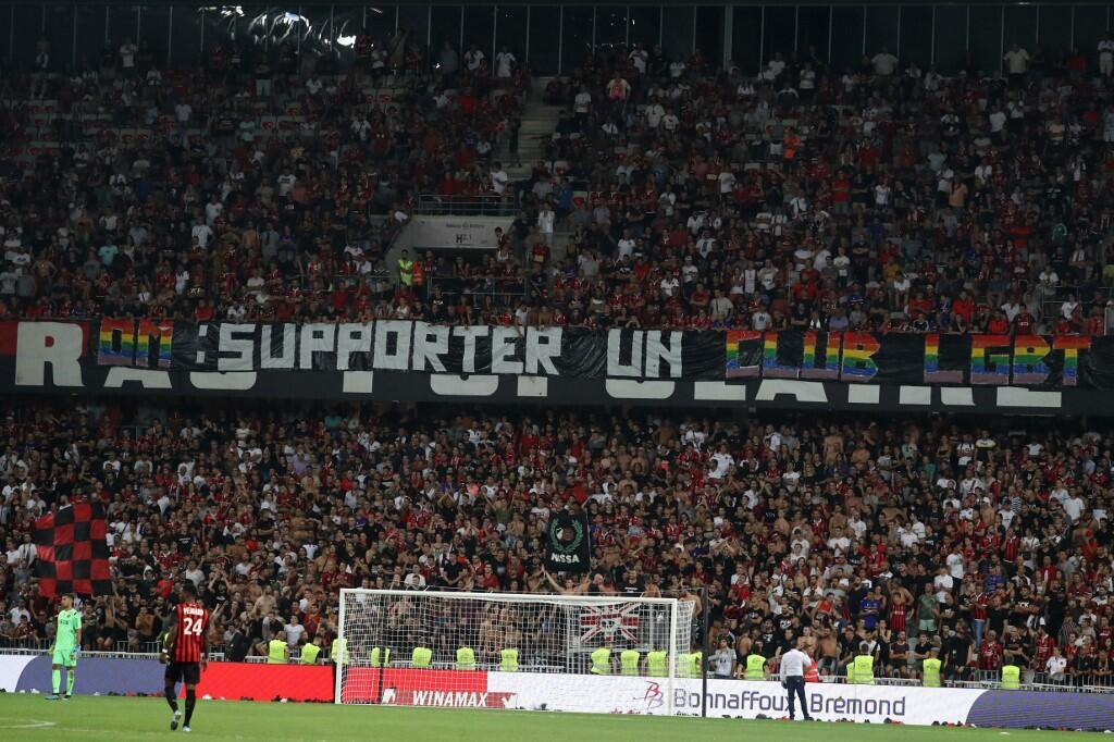 """Nice's supporters display a banner reading """"OM: support an LGBT team to fight against homophobia"""" during the French L1 football match between OGC Nice and Olympique de Marseille (OM) on August 28, 2019 at the """"Allianz Riviera"""" stadium in Nice."""