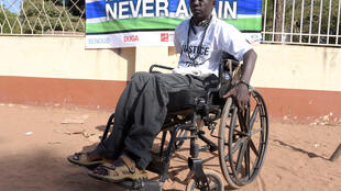 Yusuf Mbye, 35, at rally in remembrance of victims of Yahya Jammeh's regime; he lost the use of his legs in 2000 during a student demonstration; he was hit in the spine by a stray bullet. April 2017