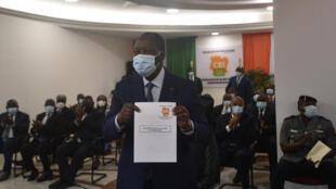 Le président ivoirien Alassane Ouattara montre son formulaire de candidature lors de la présentation de sa candidature à la présidence des prochaines élections, au siège de la CEI à Abidjan, le 24 août 2020.