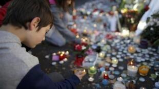 Des jeunes allument des bougies en mémoire aux victimes des attaques du Bataclan, le 15 novembre 2015.