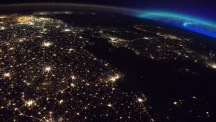 Vue de l'Europe depuis l'espace, avec Berlin au premier plan, mais aussi avec des aurores boréales au loin.