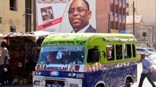 Un minibus passe devant un portrait géant de Macky Sall, à Dakar, le 4 février 2019.