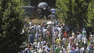 A security officer tries to protect Serbian Prime Minister Aleksandar Vucic with an umbrella as he is stoned at Srebrenica