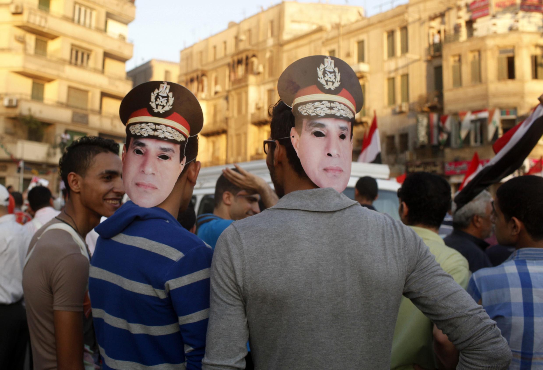 Des partisans du général al-Sissi portant des masques à son effigie, sur la place Tahrir. Le Caire, le 26 juillet 2013.