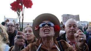 Mulher grita slogans contra a austeridade enquanto segura cravos vermelhos na praça do Comércio, em Lisboa, neste sábado, 2 de março.