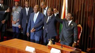 A l'Assemblée nationale de Côte d'Ivoire, mardi 10 janvier au matin, le président Alassane Ouattara (C) félicite le nouveau et premier vice-président de la Côte d'Ivoire (G), aux côtés du président de l'Assemblée nationale, Guillaume Soro.