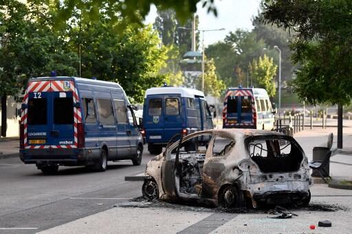 Carros da polícia francesa passam ao lado de carro incendiado no bairro de Grésilles, em Dijon.