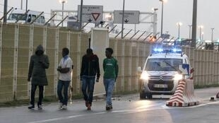 Migrants followed by police outside the port at Calais