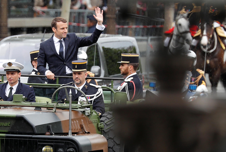 O presidente Emmanuel Macron desfila em um veículo militar aberto na avenida Champs Elysées em direção ao Arco do Triunfo.