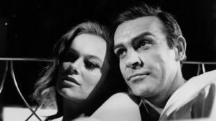 """L'acteur Sean Connery, dans le rôle de James Bond, aux côtés de l'actrice italienne Luciana Paoluzzi, lors d'une scène dans le film """"Thunderball"""", ou """"Opération Tonnerre"""", photo prise le 16 mars 1965, en Angleterre."""