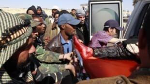 Повстанцы несут раненого в Адждабии 10 апреля 2011 г.