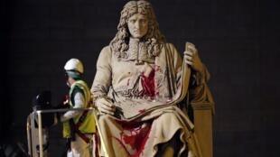 Un employé nettoie la statue de Jean-Baptiste Colbert, devant l'Assemblée nationale à Paris, en partie recouverte le 23 juin 2020 de peinture rouge au torse et aux jambes et d'une inscription «—Négrophobie d'État—».