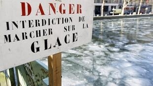 A sign posted near the partially frozen Saint Martin canal in Paris