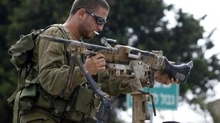 Un soldado israelí sostiene una ametralladora encima de tanque cerca de la frontera con Líbano