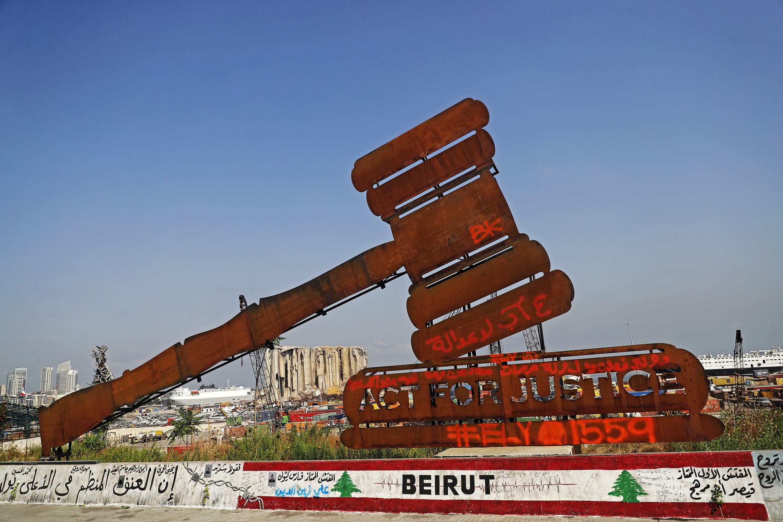 Escultura a simbolizar a justiça com o porto de Beirute como pano de fundo. 4 de Agosto de 2021.