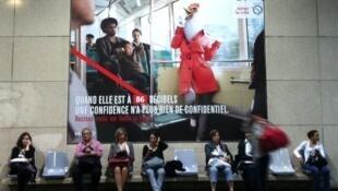 Cartaz na estação de Luxembourg, em Paris, mostra mulher com cabeça de galinha falando alto no celular.