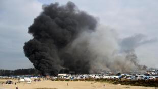 D'épaisses fumées noires s'élèvent au-dessus du camp de Calais, ce mercredi 26 octobre, après midi.