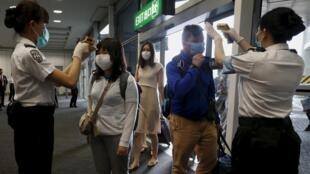 Funcionários em um aeroporto da Coréia do Sul controlam a temperatura dos passageiros, antes do embarque.