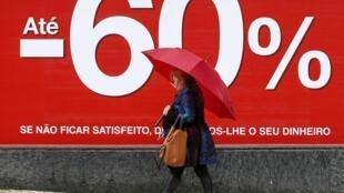 Mulher caminha diante de anúncio de descontos em Lisboa. FMI recomenda amplos cortes no funcionalismo público