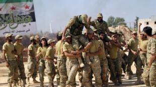 Các chiến binh nổi dậy công kênh người hướng dẫn khi kết thúc đợt huấn luyện ở Hama, Syria, 31/03/2016.