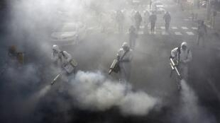 نیروهای آتش نشانی جمهوری اسلامی ایران برای مبارزه با ویروس کرونا با استفاده از مواد ضدعفونی کننده یکی از خیابانهای تهران را شتشو میکنند - ١٣ مارس ٢٠٢٠