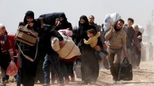 Famílias sírias fogem da localidade de Hammouriyeh, cercada pelos tanques sírios em Guta Oriental.