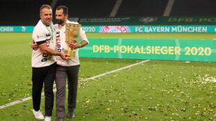 L'entraîneur du Bayern Munich Hansi Flick (g) et le directeur sportif Hasan Salihamidzic après la victoire du club en finale de la Coupe d'Allemagne, le 4 juillet 2020 à Berlin