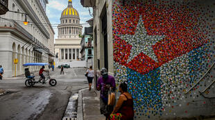 People talk near a graffiti with the Cuban flag in a street of Havana, on July 12, 2021.Thousands of Cubans took part in rare protests Sunday against the communist government.