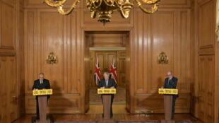 Le Premier ministre britannique Boris Johnson, encadré par Jonathan Van-Tam, médecin-chef adjoint, et Patrick Vallance, conseiller scientifique en chef, en conférence de presse le 27 janvier 2021.