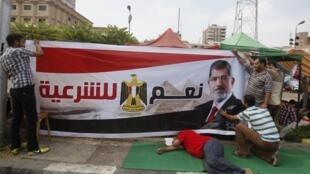 Des manifestants pro-Morsi expriment leur soutien en brandissant des portraits du président égyptien.