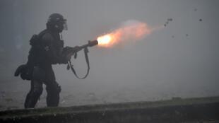 Un policía antidisturbios lanza un proyectil de gas lacrimógeno a los manifestantes durante una protesta contra la reforma fiscal, el 3 de mayo de 2021 en la ciudad colombiana de Cali