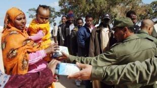 Les soldats à travers les Nations-Unies distribuent de la nourriture pour les refugiés libyens qui se sont exilés en Tunisie, le 23 mars 2011.