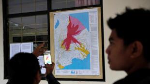 A Rendang, dans un centre d'études scientifiques, des personnes prennent en photo la carte des zones à risque situées autour du volcan Agung.