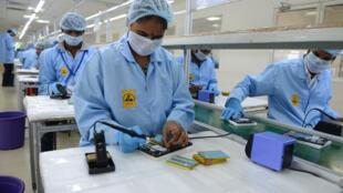Des techniciens, dont une femme au premier plan, travaillent sur des circuits intégrés pour le compte de l'entreprise canadienne DataWing à Hyderabad, en Inde (illustration).